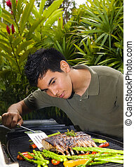 Asian American man grilling lamb chops - A young Asian...