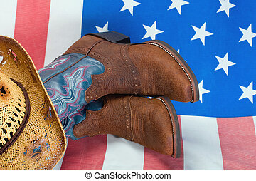 cowboy boots and straw hat on American flag background