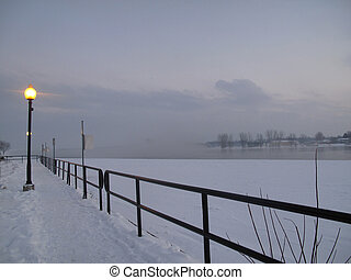 Lamplight on winter walkway with railing by the waterfront...