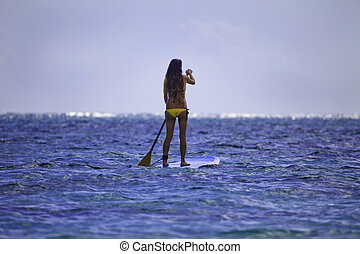 young japanese woman in a bikini with her paddle board in...