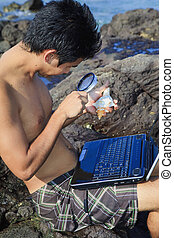 young asian man studies a seashell with his magnifying glass...