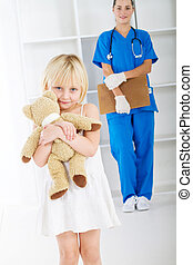 little patient holding teddy bear - little girl holding...