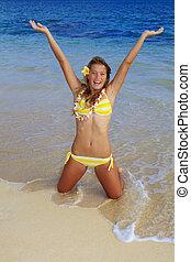 teenage girl in a bikini at a hawaii beach wearing a lei