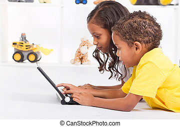 brother and sister playing laptop - African American brother...