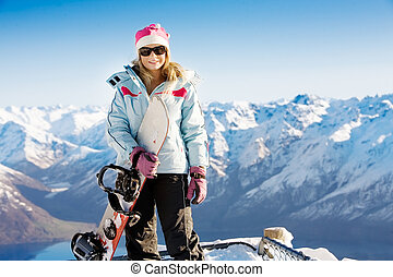 Snowboard girl - Woman holding snowboard with mountains in...