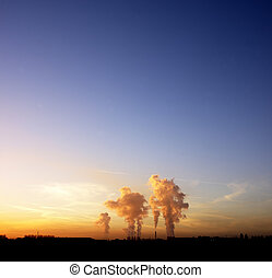 industrial cooling towers at sunset