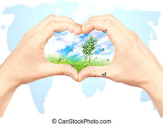 Human hand and nature on world map background.
