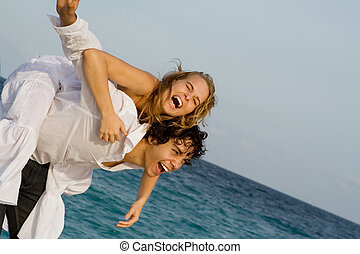 happy piggyback couple on spring break or summer vacation