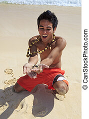 local man holds up a sand crab