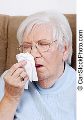sick senior sneezing into a tissue