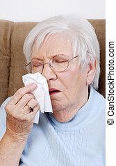 sick senior sneezing into a tissue