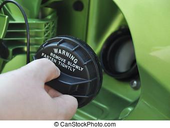 Filling petrol - Closeup of female hand holding petrol cap.