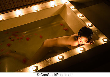 Candlelit bath - Beautiful Asian girl lays in candle lit...
