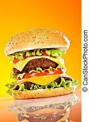 Tasty and appetizing hamburger on a yellow background
