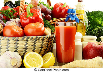 Raw vegetables with glass of juice and kitchen dishes -...