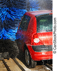 Car Wash - A red car being washed by automatic machine