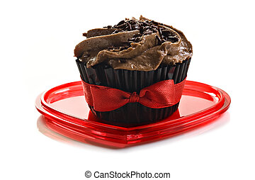 Chocolate cupcake with red bow on a heart shaped plate