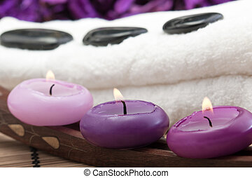 hotstones on towel with purple candles - black hotstones on...
