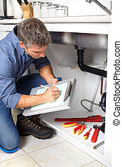 Plumber. - Young plumber fixing a sink at kitchen.