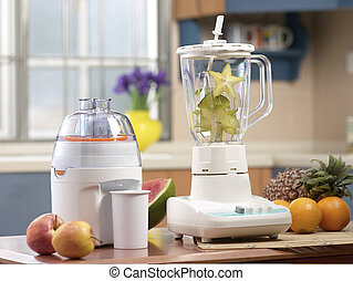 Juice extractor - kitchen machine and fruits on kitchen...