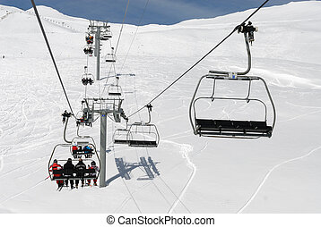 chairlift mountain - Skiers on chairlift at ski resort