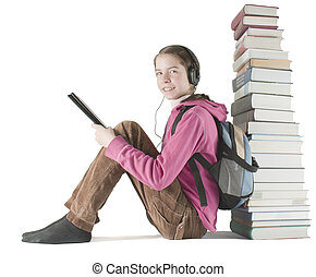 Teen girl reads ebook sitting near the stack of printed...