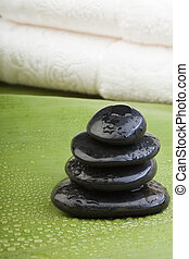 wet spa hotstones on green leaf - wet spa hotstones with...