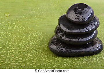 wet hotstones on green banana leaf - wet volcanic hotstones...