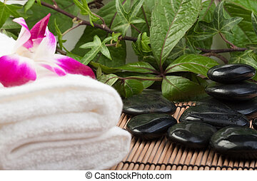 tropical massage - white towel, orchid and hotstones in...