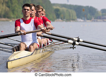 Rowing team during the start - Coxed four rowing team during...