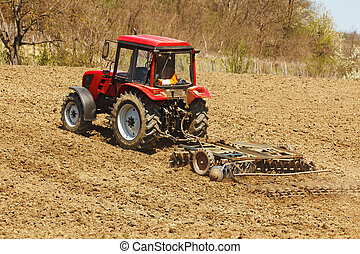 Tractor with disk harrow and rake - Red tractor on hill with...