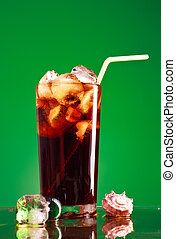 Cola Glass - glass of cola with ice and straw on green...