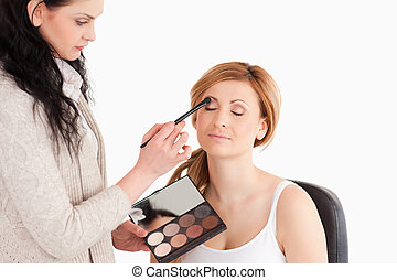 Young woman being made up by a make-up artist in a studio