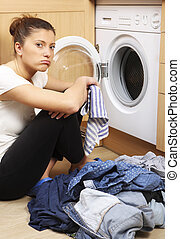 Housewife doing laundry - A close up of a young tired wife...