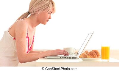 Attractive woman surfing on her laptop while having her...