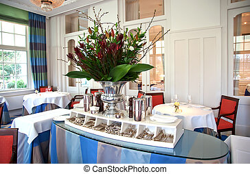 classic restaurant - flowers and table with silver in...
