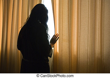 depressed woman by window - A silhouette of a depressed and...