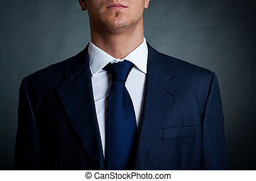 Closeup shot of business suit on a man, over dark background