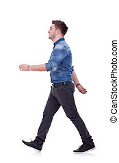 side view of a young casual man walking forward over white