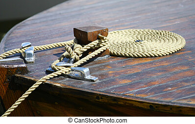 Boat rope on dock - Coiled mooring line tied around cleat on...