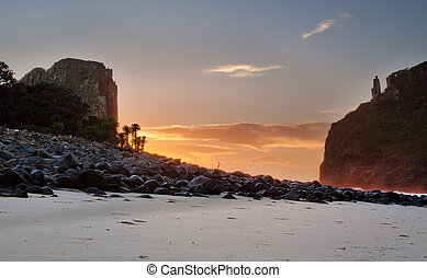 Sunrise landscape on the beach with rocks and cliffs clouds