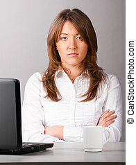 business woman is sitting in the office with laptop