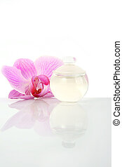 Perfume bottle and orchid flower, isolated on white