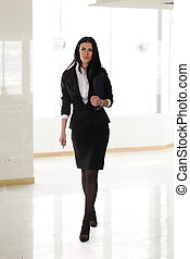 A pretty business woman walking indoor, modern business...