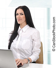 beautiful confident businesswoman working on laptop in office