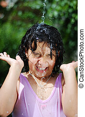 Splashing water in summer, cute girl playing outdoor in nature