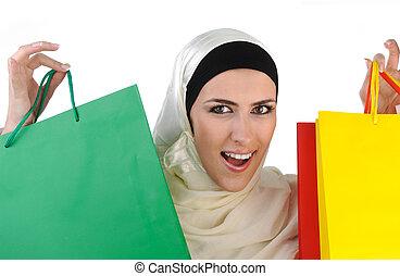 Beautiful Muslim traditional but modern woman holding...