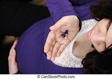 Pregnant woman with tablets in hands