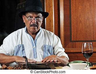 man making luxury handmade cuban cigare - older senior man...