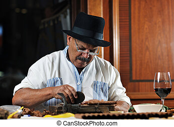 man making luxury handmade cuban cigare - older senior man...